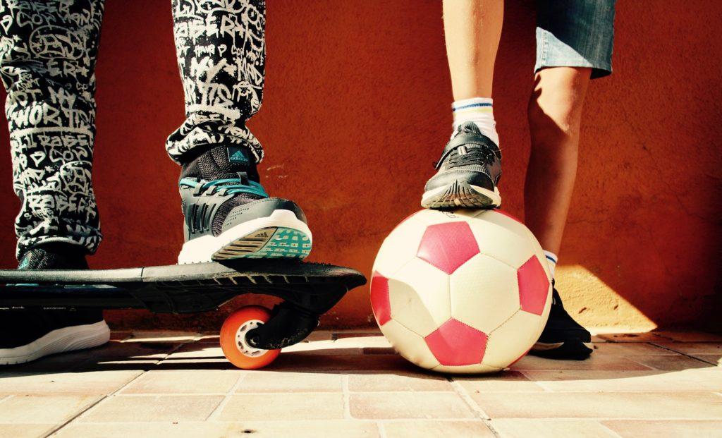 bimbi con skateboard e pallone